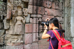 Tourist at Angkor Wat. Photographer / Tourist photographing the wall sculpture at the ancient Angkor Wat, Siem Reap, Cambodia stock photos