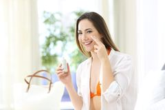 Tourist applying sunscreen protection on summer vacations. Tourist applying sunscreen protection on her face in an hotel room on summer vacations royalty free stock image