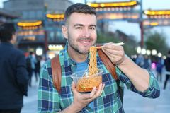 Tourist in Asia eating noodles outdoors.  royalty free stock image