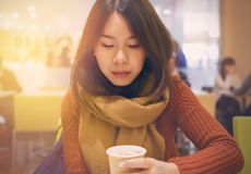 Tourist Asian lady drinking coffee or tea in a coffee shop. Vintage tone and Soft light processed.  Stock Photos
