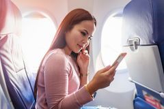 Tourist asian woman sitting near airplane window at sunset and using mobile phone during flight. Thailand royalty free stock photo