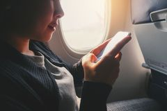 Tourist Asian woman sitting near airplane window and using Smart phone during flight stock photography