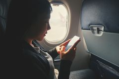 Tourist Asian woman sitting near airplane window and using Smart phone during flight royalty free stock photos