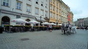 Tourist attractions in old Krakow, Poland. KRAKOW, POLAND - JUNE 13, 2018: The riding horse-drawn carriages attract the tourists to take a tour along the city stock video footage