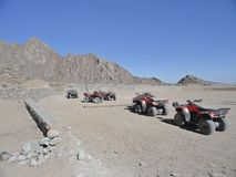Tourist attractions - riding a quad bike on a rocky desert royalty free stock photo