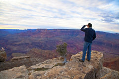 Tourist auf dem Rand von Grand Canyon Stockfotografie