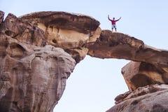Tourist auf Felsen Wadi Ram-Wüste Entsteinen Sie Brücke Jordanien-Landschaft lizenzfreies stockfoto