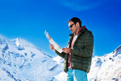 Tourist on the background of snowy mountains. Man with a map looking forward to the background of snowy mountains. Grossglockner, Austria Royalty Free Stock Image