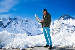 Tourist on the background of snowy mountains. Man with a map looking forward to the background of snowy mountains. Grossglockner, Austria Royalty Free Stock Photos