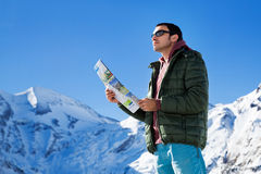 Tourist on the background of snowy mountains. Man with a map looking forward to the background of snowy mountains. Grossglockner, Austria Royalty Free Stock Photography