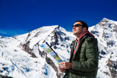 Tourist on the background of snowy mountains. Man with a map looking forward to the background of snowy mountains. Grossglockner, Austria Stock Image