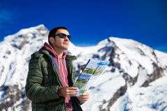 Tourist on the background of snowy mountains. Man with a map looking forward to the background of snowy mountains. Grossglockner, Austria Royalty Free Stock Photo
