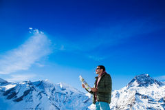 Tourist on the background of snowy mountains. Man with a map looking forward to the background of snowy mountains. Grossglockner, Austria Stock Photography