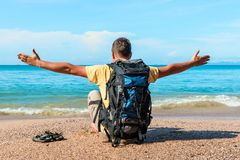 A tourist with a backpack with arms spread out to the sides sits. On the sand near the sea Royalty Free Stock Images