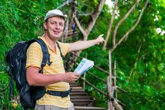 Tourist with a backpack in the Asian jungle. In the hike shows the direction of the route Royalty Free Stock Image