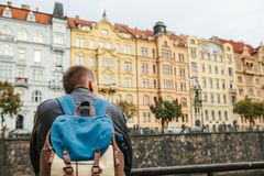 A tourist with a backpack on the backdrop of the old architecture in Prague in the Czech Republic. Travel, tourism. A tourist with a backpack on the backdrop of Stock Photos
