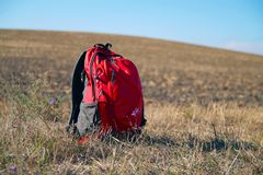 Tourist backpack on the background of a plowed field in autumn. Daylight, clear sky Royalty Free Stock Photos