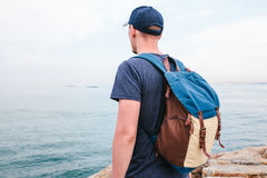 A tourist with a backpack on the coast. Travel, tourism, recreation. A tourist with a backpack on the coast. Travel, tourism Stock Photo