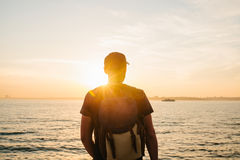 A tourist with a backpack on the coast. Travel, tourism, recreation. On the Sunset. A tourist with a backpack on the coast. Travel, tourism. On the Sunset Stock Photo