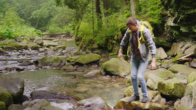 A tourist with a backpack crosses a mountain river over rocks. The dangerous moment - almost falls, slips. Dangerous stock video footage