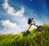 Tourist. With backpack crossing rocky terrain with grass at sunny day Royalty Free Stock Photo