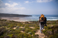 Tourist with backpack on the edge of a beautiful cliff near the ocean Portugal Algarve Royalty Free Stock Photography