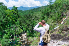 The tourist with a backpack examines vicinities from the mountain. Travel on a rainforest royalty free stock photography