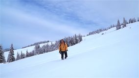 A tourist walks through the snow in the mountains. stock video footage