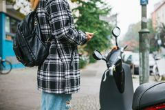 A tourist with a backpack is going to use an electric scooter through a mobile application in the phone and distally. Activate it. A popular vehicle in Berlin Stock Photo