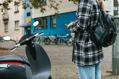 A tourist with a backpack is going to use an electric scooter through a mobile application in the phone and distally. Activate it. A popular vehicle in Berlin Stock Photography