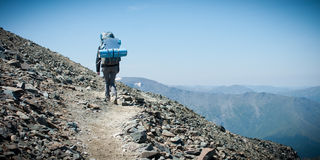 Tourist with a backpack going up the mountain path, pass Karaturek. Trekking in the Altai Mountains Stock Photos