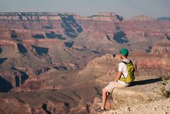 Tourist with backpack at Grand Canyon. Sitting on the rock edge, Arizona, USA Stock Photo