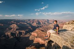 Tourist with backpack at Grand Canyon. Sitting on the rock edge, Arizona, USA Royalty Free Stock Image