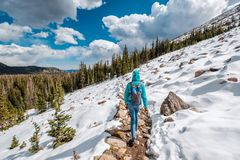 Tourist with backpack hiking on snowy trail Stock Images