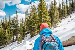 Tourist with backpack hiking on snowy trail Stock Photo