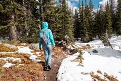 Tourist with backpack hiking on snowy trail Royalty Free Stock Photos