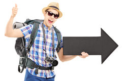 Tourist with backpack holding a big black arrow and giving thumb Royalty Free Stock Image
