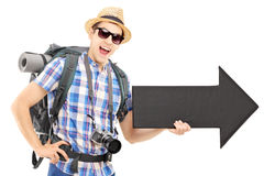 Tourist with backpack holding a big black arrow Stock Image