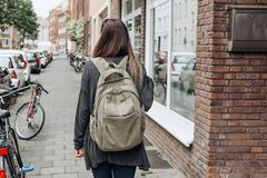 Tourist with a backpack is looking for booked online accommodation in an unfamiliar city. Or a student girl with a backpack is walking through the city royalty free stock images