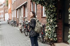 Tourist with a backpack is looking for booked online accommodation in an unfamiliar city. Or a student girl with a backpack is walking through the city stock photography
