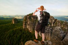 Tourist with backpack make frame with fingers on both hands. Hiker with big backpack stand on rocky view point above forest. Royalty Free Stock Photo