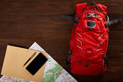 Tourist backpack with map, notebook, pen and telephone on the wooden background. Orange tourist backpack with map, notebook, pen and telephone on the wooden royalty free stock photography