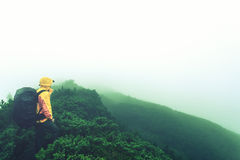 Tourist with backpack in the misty mountains Royalty Free Stock Photography