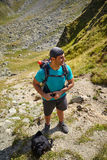 Tourist with backpack on mountain Royalty Free Stock Photos