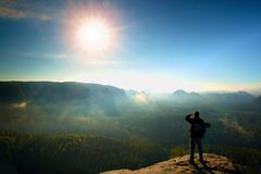 Tourist with backpack and poles on  rocky peak. Sunny day, dreamy fogy valley below Royalty Free Stock Images