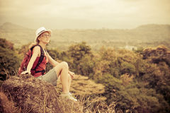 Tourist with backpack relaxing on rock and enjoying admiring the Royalty Free Stock Photos