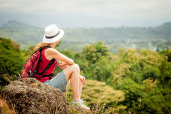 Tourist with backpack relaxing on rock and enjoying admiring the Stock Photos