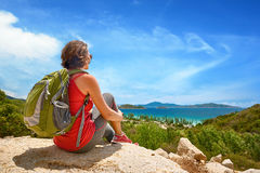 Tourist with backpack relaxing on top of the mountain and enjoyi Royalty Free Stock Photography