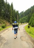 Tourist with a backpack rises in the mountains on summer. Ukraine royalty free stock photography