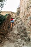 Tourist with a backpack rises up the path. Tourist girl with a backpack rises up the ruins of the old fortress royalty free stock photography